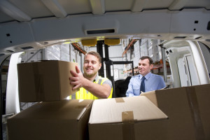 Warehouse worker loads a delivery van as his manager stands in the background.